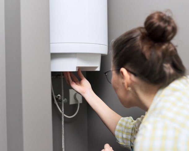 home-water-heater-woman-regulates-the-temperature-on-an-electric-picture-id1272654657-min
