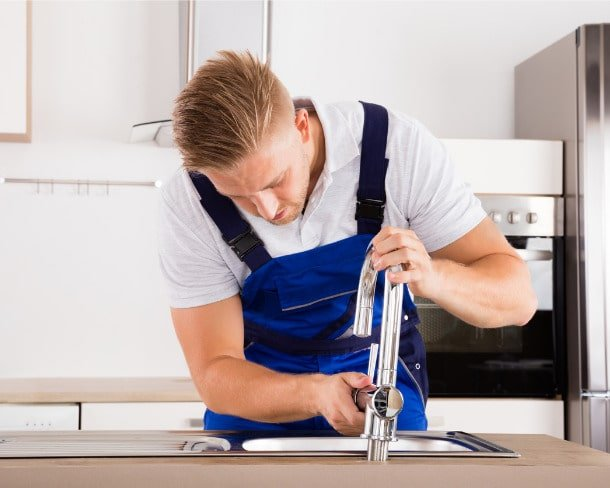 plumber-fixing-faucet-in-kitchen-picture-id832983328-min