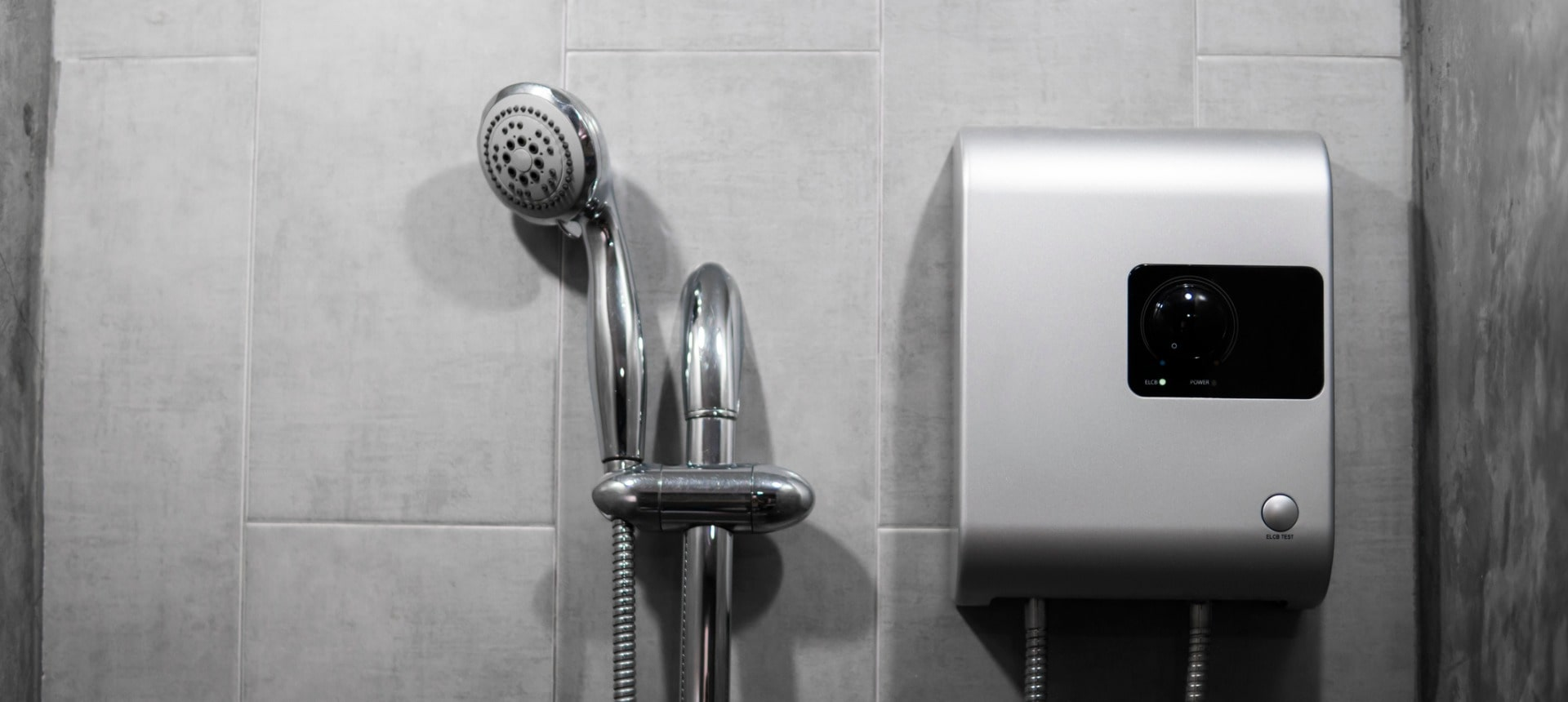 instant-tankless-electric-water-heater-installed-on-grey-tile-wall-picture-id1198616760-min