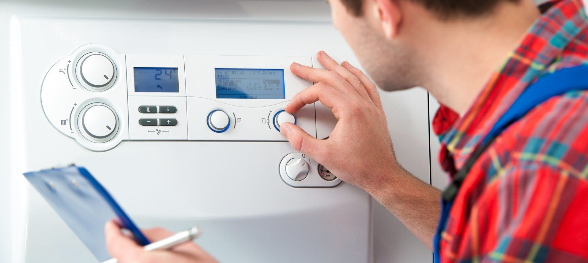 man-in-a-flannel-shirt-works-on-a-gas-boiler-picture-id482115591-min