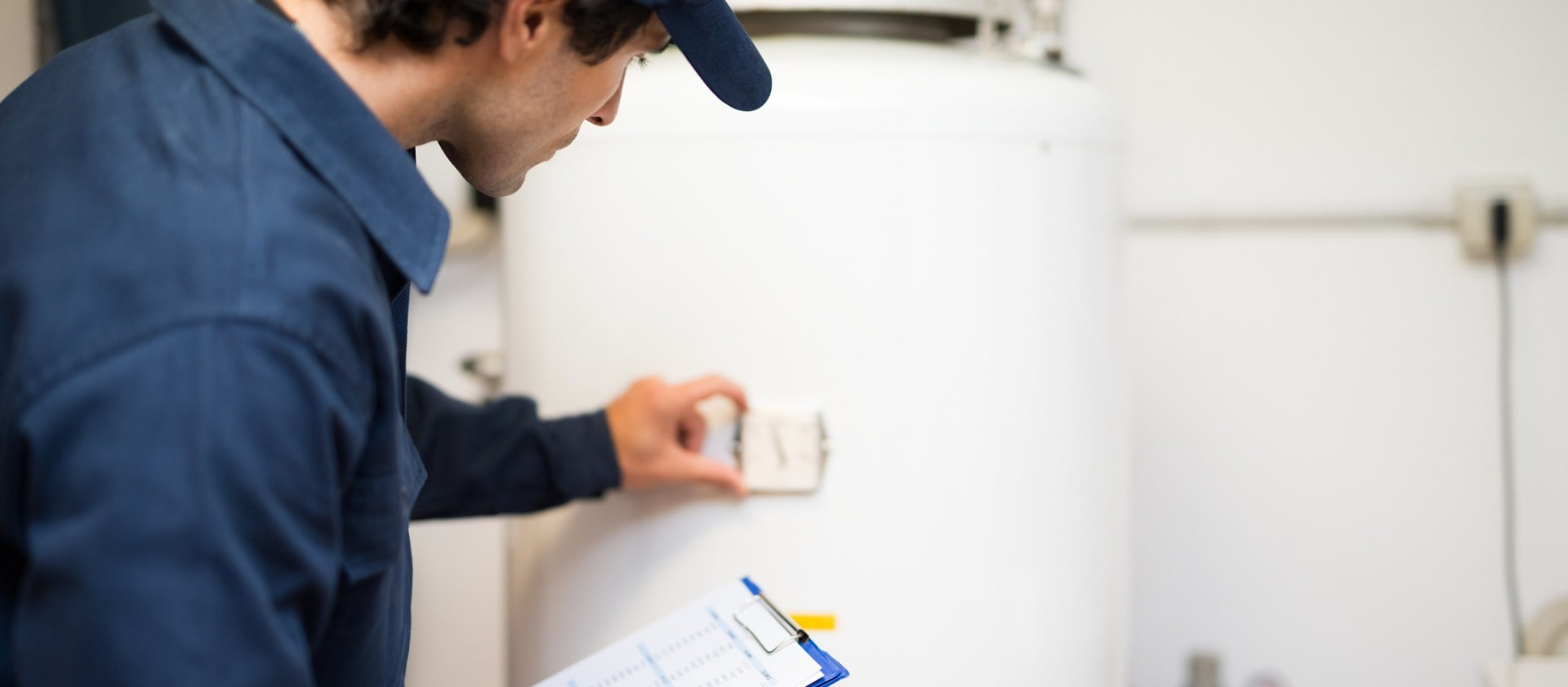 plumber-repairing-an-hotwater-heater-picture-id597967152-min