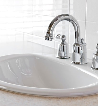 closeup-of-white-bathroom-vanity-with-silver-faucet-picture-id121370055-min