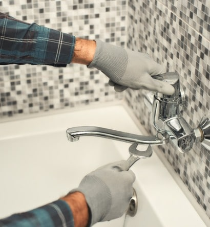 plumber-repairing-a-tap-in-the-bathroom-picture-id1170038016-min